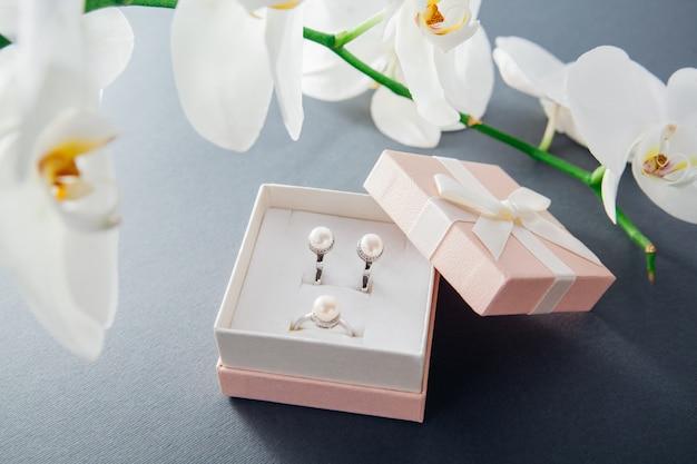 Anello e orecchini in argento con perle in confezione regalo con fiore orchidea bianca. presente per le vacanze. accessori alla moda Foto Premium