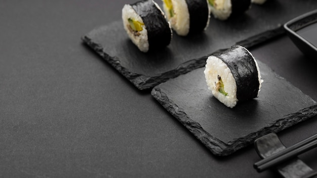 Angolo alto dei rotoli di sushi sull'ardesia con lo spazio della copia Foto Gratuite
