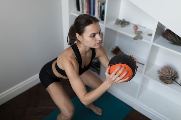 Angolo alto della donna che fa le esercitazioni con la sfera Foto Gratuite