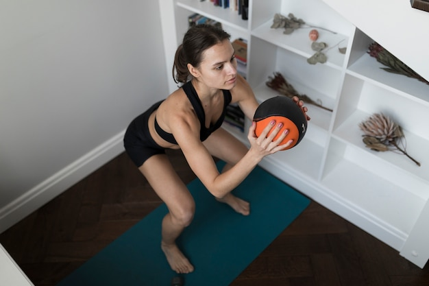 Angolo alto della donna sportiva che si esercita con la palla medica Foto Gratuite