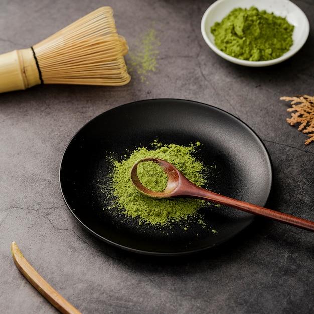 Angolo alto della polvere del tè di matcha sul piatto con il cucchiaio di legno Foto Gratuite