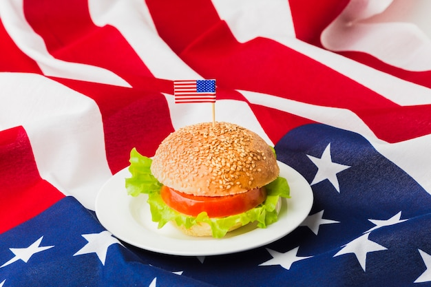 Angolo alto di hamburger sul piatto con la bandiera americana Foto Gratuite
