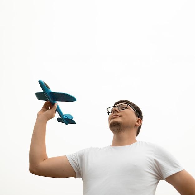 Angolo basso del giovane che tiene un aeroplano Foto Gratuite