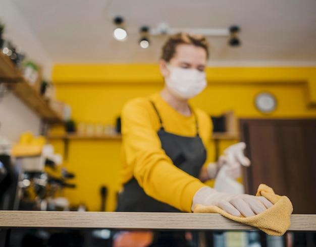 Angolo basso di pulizia femminile di barista con la mascherina medica sopra Foto Gratuite