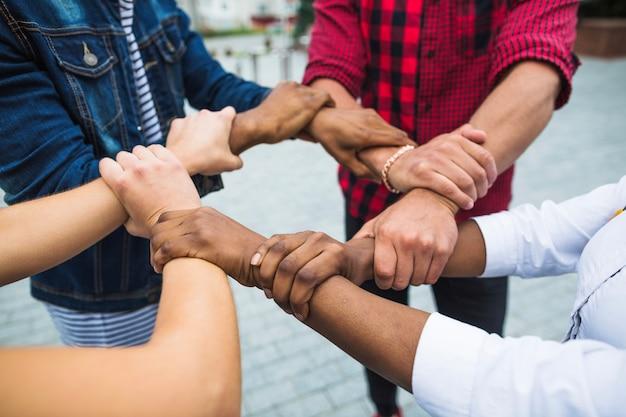 Anonima gente multirazziale impilando le mani Foto Gratuite