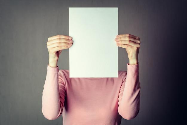 Anonimo donna che copre il viso con un foglio di carta bianco Foto Premium