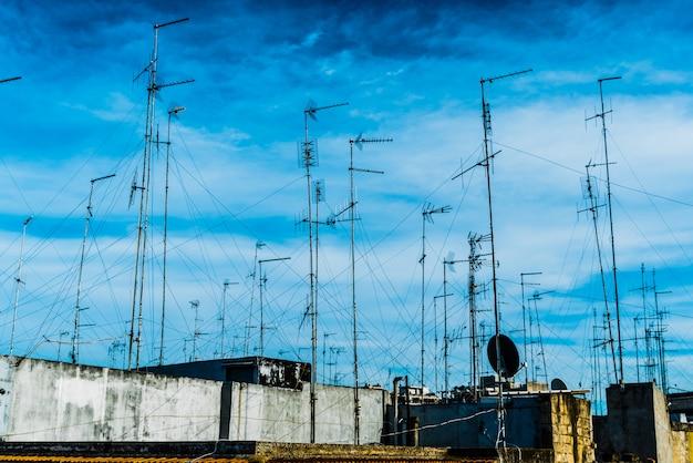 Antenne televisive sul tetto di un vecchio edificio con cielo drammatico. Foto Premium