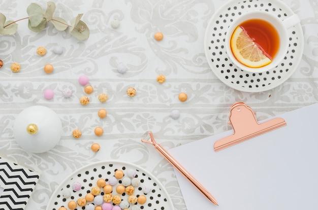 Antica penna su appunti con caramelle e tazza di tè al limone e zenzero sulla tovaglia Foto Gratuite