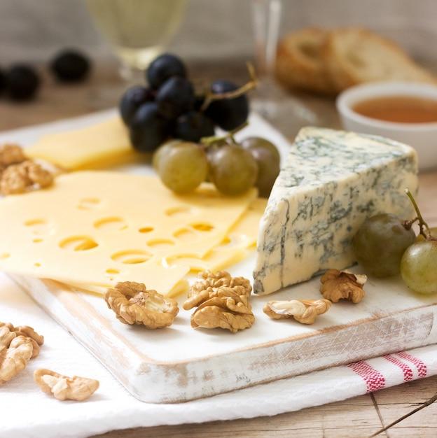 Antipasti di vari tipi di formaggio, uva, noci e miele, serviti con vino bianco e rosso Foto Premium