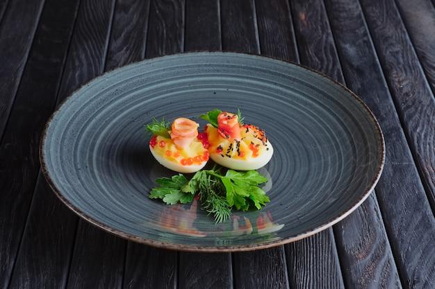 Antipasto per la ricezione. uovo con prosciutto e caviale Foto Premium