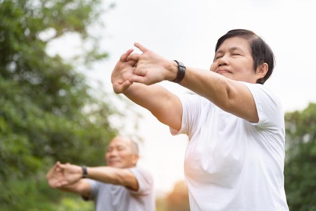 Anziani che allungano le mani, le braccia prima dell'esercizio al parco. coppie senior asiatiche felici che godono dell'allenamento ad all'aperto di mattina. Foto Premium