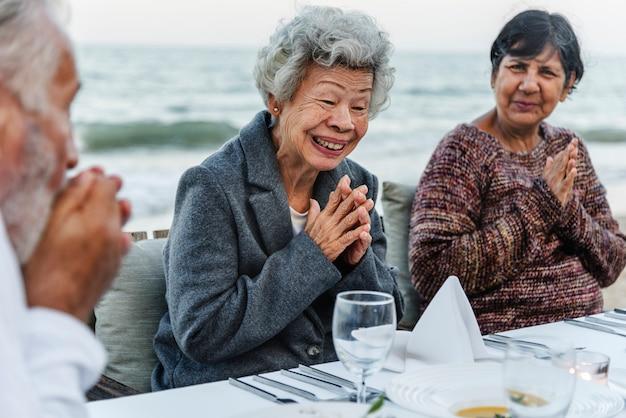 Anziani che hanno una cena in spiaggia Foto Premium