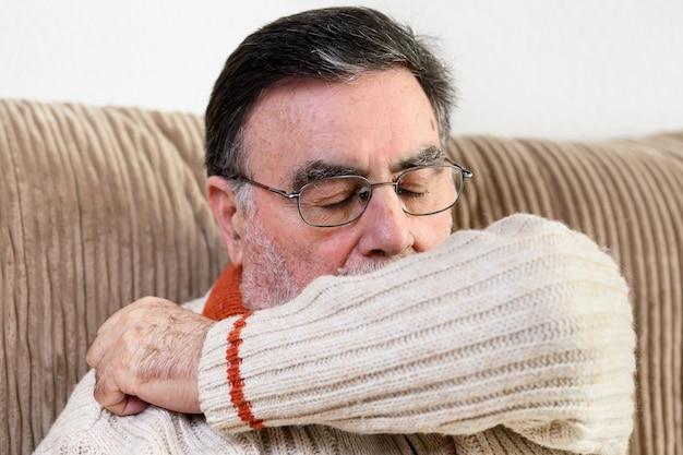 Anziani che starnutiscono, tossiscono nella manica o nel gomito per prevenire la diffusione di covid-19. Foto Premium