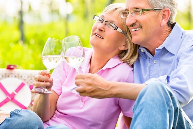 Anziani felici che mangiano picnic bevendo vino Foto Premium