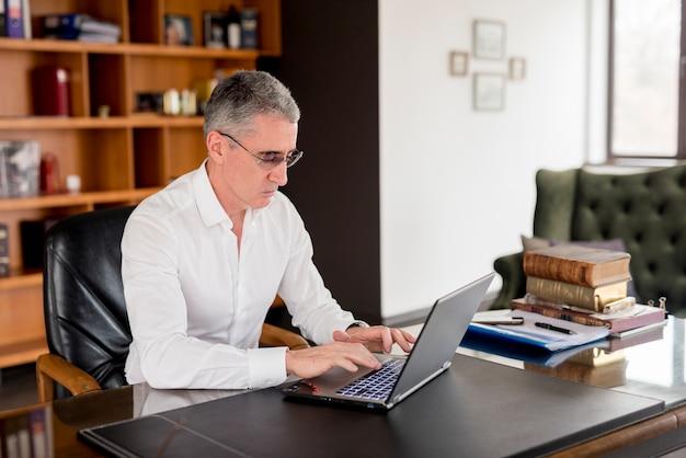 Anziano, uomo affari, usando, suo, laptop Foto Gratuite