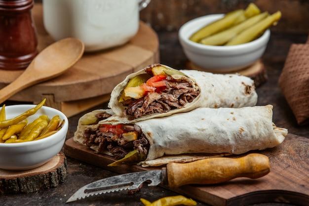 Ape alla griglia avvolgere doner con cetrioli, pomodori e patatine fritte Foto Gratuite