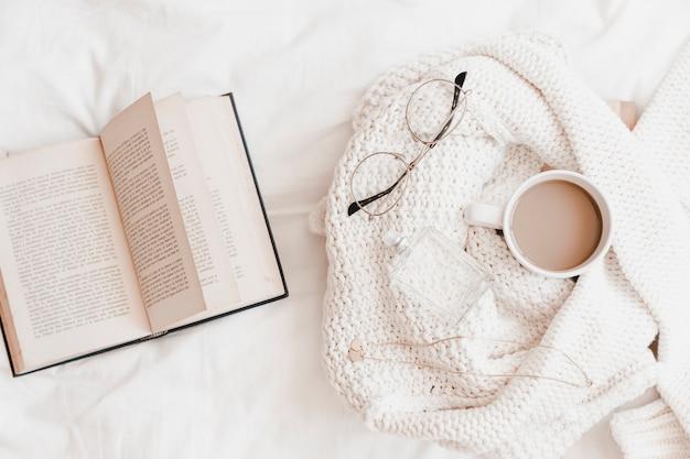 Aperto romanzo vicino maglione con le cose sul lenzuolo Foto Gratuite