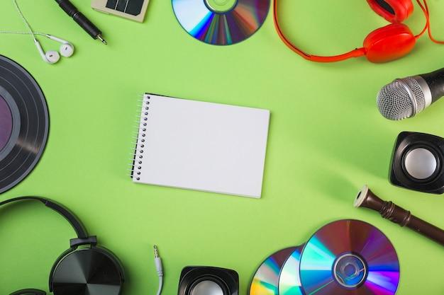 Apparecchiature audio intorno al blocco note vuoto spirale su sfondo verde Foto Gratuite