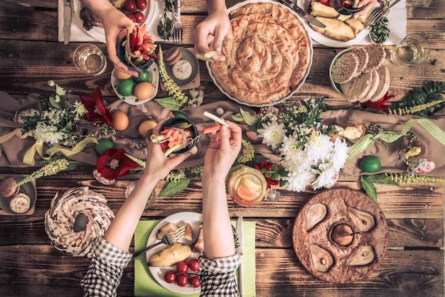 Appartamento-festa di amici o familiari al tavolo festivo con carne di coniglio, verdure, torte, uova, vista dall'alto. Foto Gratuite