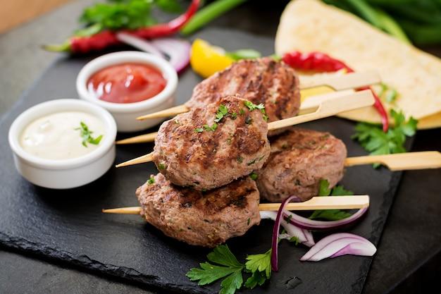 Appetitoso kebab di kofta (polpette) con salsa e tortillas di tacos sul tavolo nero Foto Gratuite
