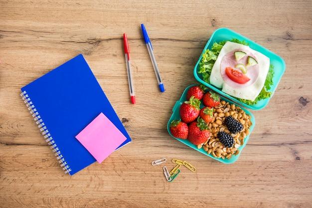 Appetitoso pranzo scolastico e articoli di cancelleria sul tavolo Foto Gratuite