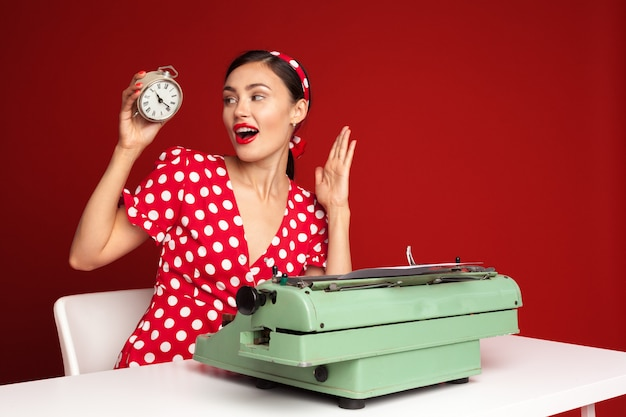 Appuntare la ragazza che scrive su una macchina da scrivere Foto Premium