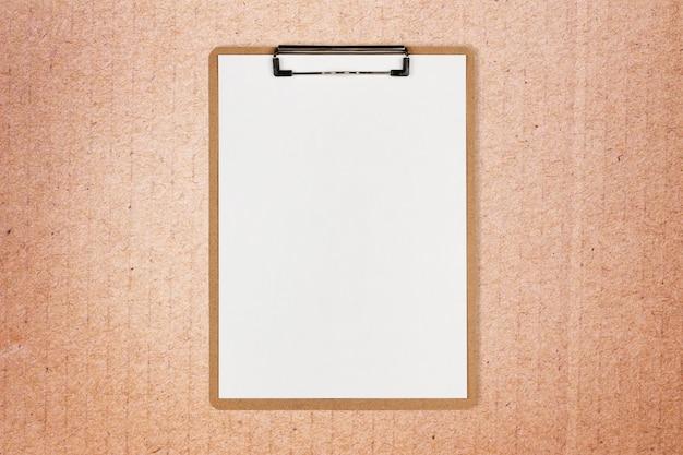 Appunti con foglio bianco e spazio per il testo su sfondo di carta artigianale Foto Premium