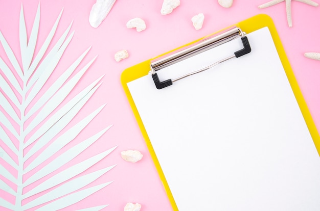 Appunti di vista superiore con un pezzo di carta e foglia di palma in bianco su sfondo rosa Foto Premium