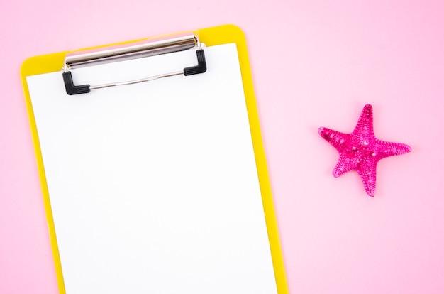 Appunti di vista superiore con un pezzo di carta e stelle marine in bianco su sfondo rosa Foto Premium