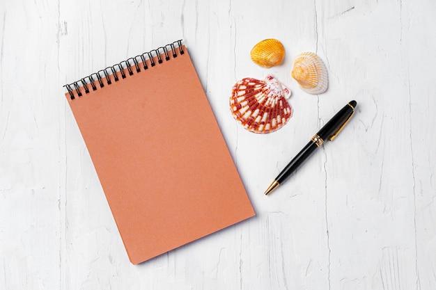 Apra il blocco note con le conchiglie su di legno bianco Foto Premium