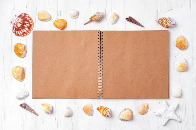 Apra il blocco note con le conchiglie su legno bianco Foto Premium