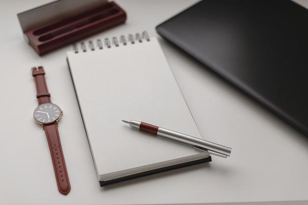 Apra il taccuino a spirale bianco con un foglio bianco e molti accessori per ufficio, un orologio da polso, un telefono cellulare, una custodia per penna e un computer portatile. Foto Premium