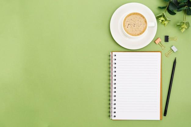 Apra il taccuino con la pagina vuota e la tazza di caffè. piano d'appoggio, spazio di lavoro su sfondo verde. posa piatta creativa. Foto Premium