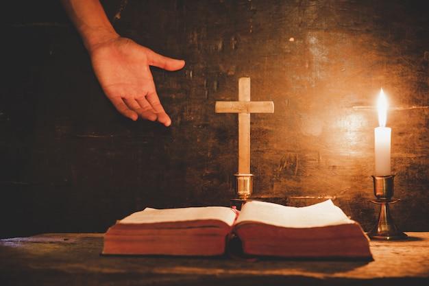 Apra la bibbia santa e la candela su una vecchia tabella di legno di quercia. Foto Gratuite