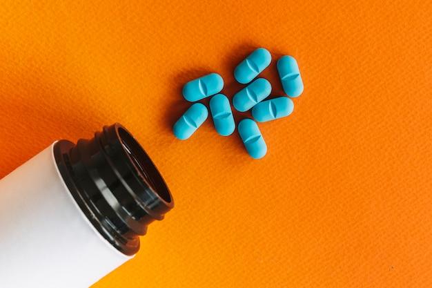 Apra la bottiglia vicino alle pillole blu su fondo arancio Foto Gratuite