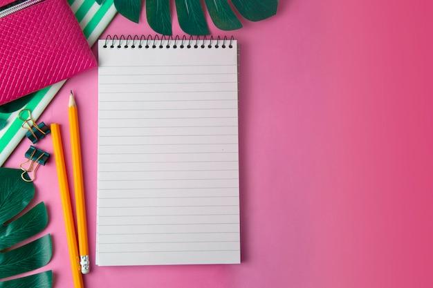 Aprire il blocco note e le foglie di monstera. modello femminile, spazio di lavoro rosa. modello. Foto Premium
