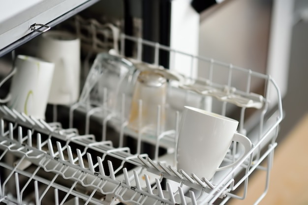 Aprire la lavastoviglie con stoviglie sporche. avvicinamento. Foto Premium