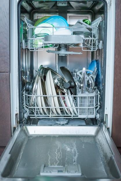 Aprire la lavastoviglie con vetri puliti e stoviglie. piatti puliti e posate in lavastoviglie. Foto Premium