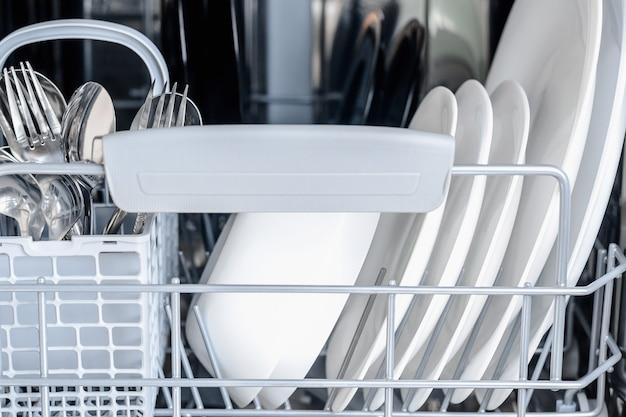 Aprire la lavastoviglie con vetri puliti e stoviglie. Foto Premium