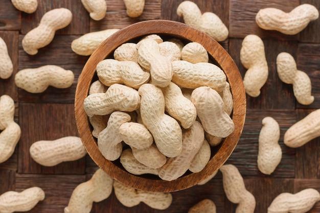 Arachidi sgusciate in ciotola di legno, vista dall'alto. Foto Premium