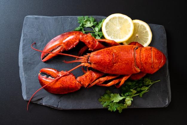Aragosta con verdure e limone sul piatto di ardesia nera Foto Premium