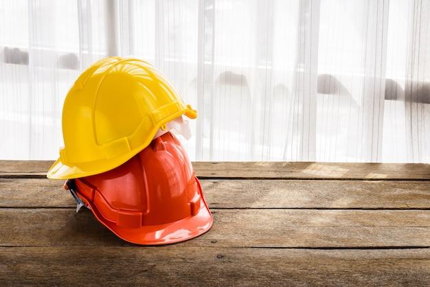 Arancione, giallo cappello di sicurezza del casco di sicurezza per il progetto di sicurezza di operaio come ingegnere o lavoratore Foto Premium