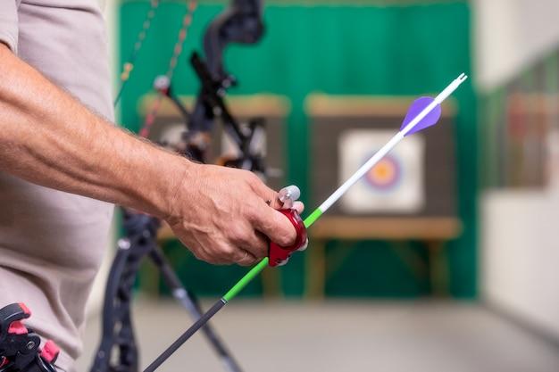 Archer tenendo l'arco raccogliendo una freccia pronta a sparare al bersaglio Foto Premium
