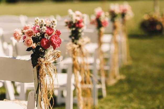 Archi di corda intrecciano mazzi di fiori rosa a sedie bianche Foto Gratuite