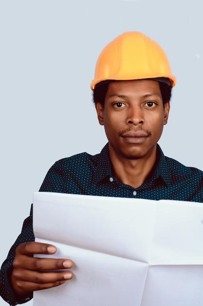 Architetto afroamericano in cappello duro con la cianografia. Foto Premium