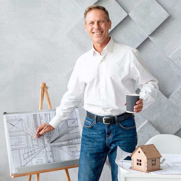 Architetto che guarda l'obbiettivo mentre mostra il suo piano Foto Gratuite