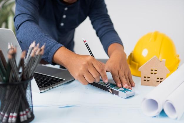Architetto che lavora e che progetta sul modello, ingegneria degli oggetti sul posto di lavoro con il computer portatile Foto Premium