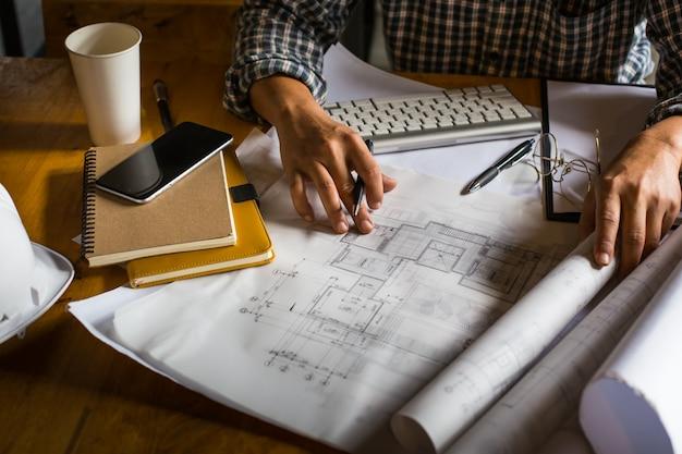 Architetto creativo che proietta sui grandi disegni nell ufficio o
