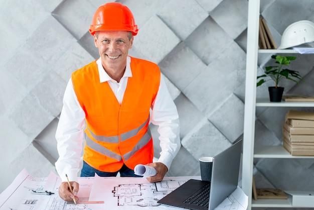 Architetto di smiley che indossa la sua attrezzatura di sicurezza Foto Gratuite