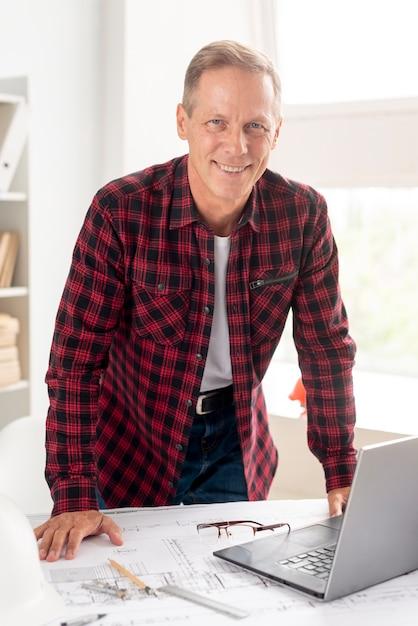 Architetto di smiley che propone alla sua scrivania Foto Gratuite